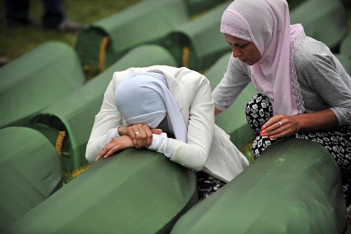 A Bosnian Muslim woman, a survivor of the Srebrenica 1995 massacre, cries by the coffin of a relative, layed out among others at the memorial cemetery in the village of Potocari near the eastern-Bosnian town of Srebrenica, on July 11, 2014 (AFP Photo/Elvis Barukcic)