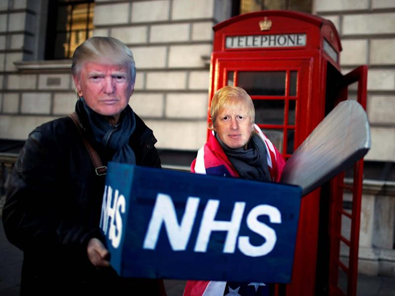 Healthcare professionals dressed as Boris Johnson and Donald Trump attend a demonstration demanding the NHS be protected from commercial exploitation: Reuters