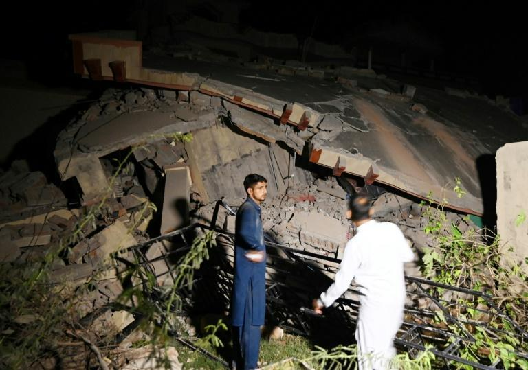 Pakistani men stand beside a collapsed building after the earthquake in Mirpur