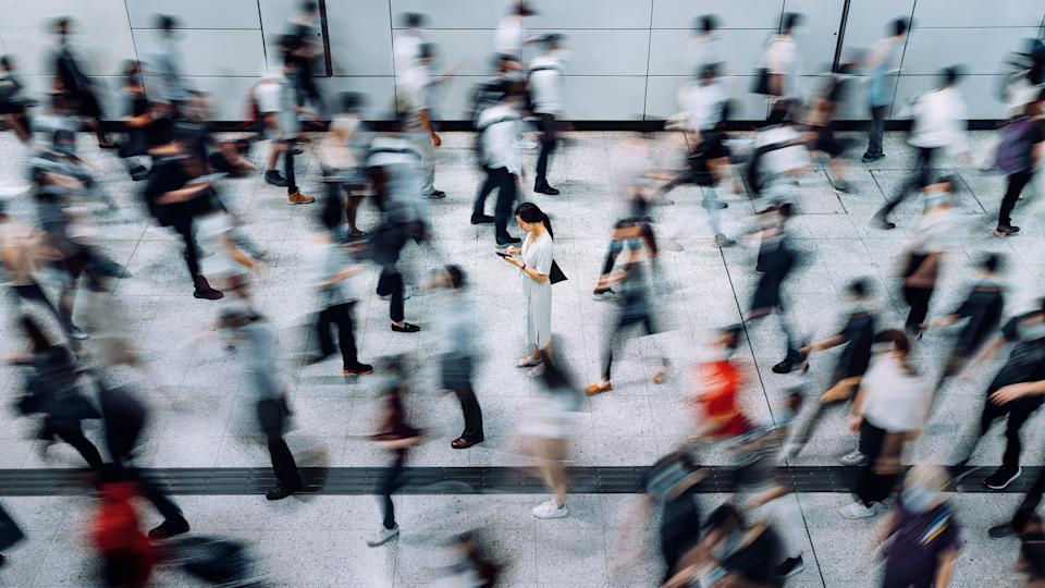 Young Asian woman using smartphone surrounded by commuters rushing by in subway station during office peak hours in the city