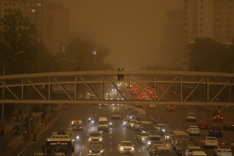 Pedestrians stand on an overpass above car traffic amid a duststorm in Beijing