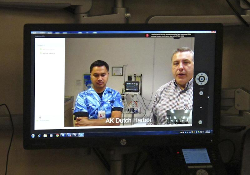 In this photo taken Sept. 13, 2016, in Anchorage, Alaska, emergency medical technician Dmitri Dela Cruz, left, and nurse practitioner James Novotny are seen on a screen at the Iliuliuk Family and Health Services on Unalaska Island during a demonstration of a new telemedicine partnership with Providence Alaska Medical Center. Beginning Thursday, Sept. 22, the Anchorage hospital will virtually beam critical care doctors 800 miles away to the emergency room of the clinic to assist staffers there during medical emergencies, thanks to a satellite link instead of the usual fiber optics. (AP Photo/Rachel D'Oro)