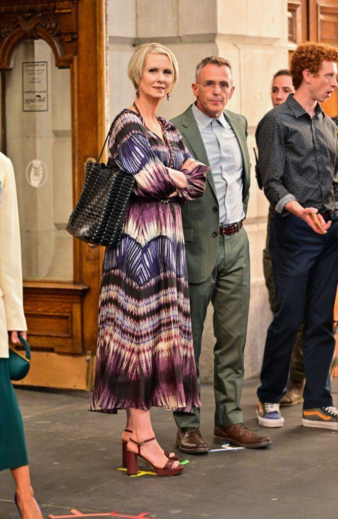 """<p>Miranda's tie dye co-ord blouse and midi skirt is from Gerard Darel, with the blouse currently on sale at John Lewis. Complimenting the look is a Paco Rabanne black bag and Gianvito Rossi 'Lena' sandals.</p><p>And, yes, that is Steve (David Eigenberg) accompanying Miranda, which we love to see.</p><p><a class=""""link rapid-noclick-resp"""" href=""""https://www.johnlewis.com/gerard-darel-nahomy-blouse-purple/p5391864"""" rel=""""nofollow noopener"""" target=""""_blank"""" data-ylk=""""slk:SHOP NOW"""">SHOP NOW</a> Gerard Darel Nahomy Blouse, Purple, £156</p><p><a class=""""link rapid-noclick-resp"""" href=""""https://go.skimresources.com?id=127X991729&xs=1&url=https%3A%2F%2Fwww.24s.com%2Fen-gb%2Flena-sandals-gianvito-rossi_GIAVHB8J%3Fgclid%3DCjwKCAjwuvmHBhAxEiwAWAYj-I9wNzBuQaRfC_MELpCKRcucPWOQYq1vwl6zExfIxDaooslNC1MDYxoCVwQQAvD_BwE%26gclsrc%3Daw.ds"""" rel=""""nofollow noopener"""" target=""""_blank"""" data-ylk=""""slk:SHOP NOW"""">SHOP NOW</a> Gianvito Rossi Lena sandals, £585<br></p><p><a class=""""link rapid-noclick-resp"""" href=""""https://www.net-a-porter.com/en-gb/shop/product/paco-rabanne/leather-tote/1266801"""" rel=""""nofollow noopener"""" target=""""_blank"""" data-ylk=""""slk:SHOP SIMILAR"""">SHOP SIMILAR</a> Paco Rabanne Leather tote, £890<br></p>"""