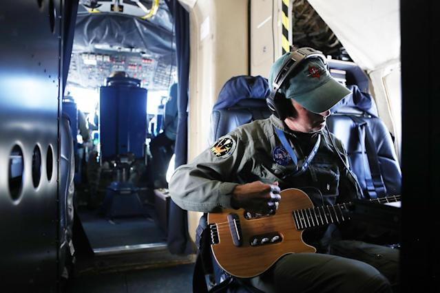 <p>NASA Operation IceBridge mission scientist John Sonntag plays his guitar after a long science flight, aboard NASA's research aircraft in the Antarctic Peninsula region, on Nov. 3, 2017. (Photo: Mario Tama/Getty Images) </p>