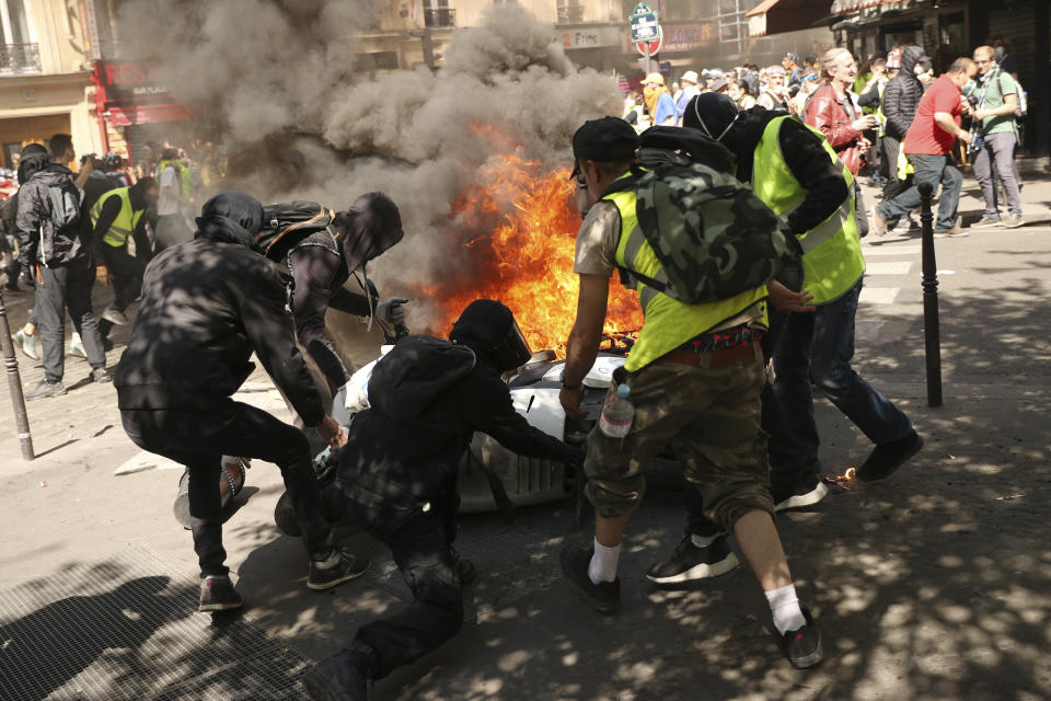 Demonstrators attend to a motorbike which was set alight during a yellow vest demonstration in Paris, Saturday, April 20, 2019. French yellow vest protesters are marching anew to remind the government that rebuilding the fire-ravaged Notre Dame Cathedral isn't the only problem the nation needs to solve. (AP Photo/Francisco Seco)