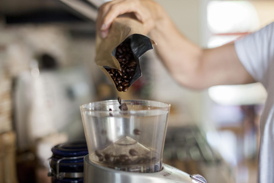 Woman pouring coffee beans in electric grinder