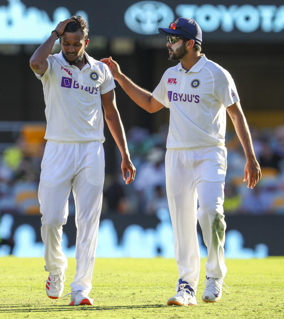 India's Thangarasu Natarajan, left, and India's Shardul Thakur talk during play on the first day of the fourth cricket test between India and Australia at the Gabba, Brisbane, Australia, Friday, Jan. 15, 2021. (AP Photo/Tertius Pickard)