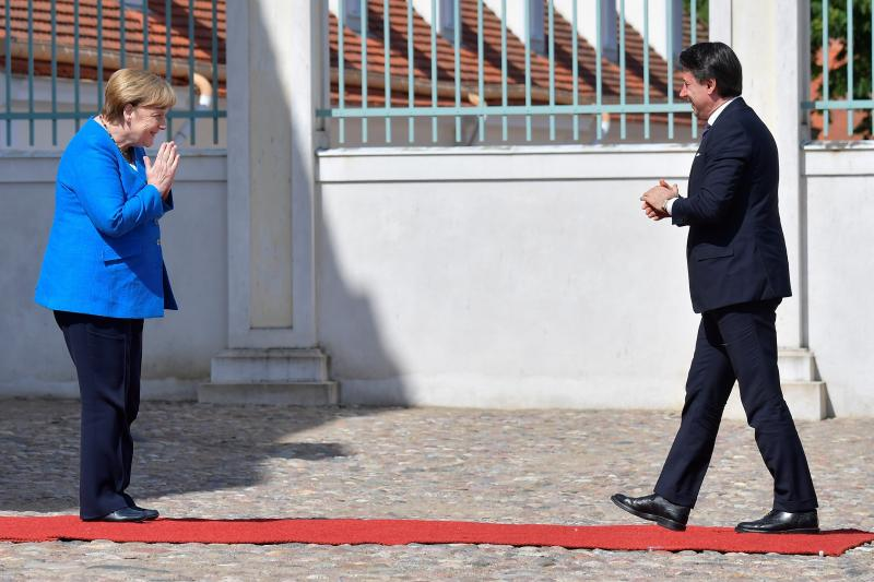 German Chancellor Angela Merkel, left, welcomes Italian Prime Minister Guiseppe Conte, right, for a meeting at the German government's guest house 'Meseberg' in Gransee, north of Berlin, Germany, Monday, July 13, 2020. (Tobias Schwarz/Pool Photo via AP)