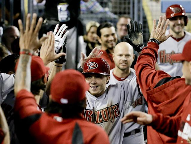 Arizona Diamondbacks' Tony Campana celebrates in the dugout after scoring on a wild pitch against the Los Angeles Dodgers during the ninth inning of a baseball game in Los Angeles, Friday, April 18, 2014. (AP Photo/Chris Carlson)