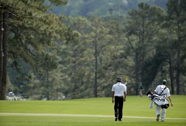 U.S. golfer Bubba Watson walks down the second fairway with his caddie Ted Scott (R) during the final round of the Masters golf tournament at the Augusta National Golf Club in Augusta, Georgia April 13, 2014. REUTERS/Mike Blake (UNITED STATES - Tags: SPORT GOLF)