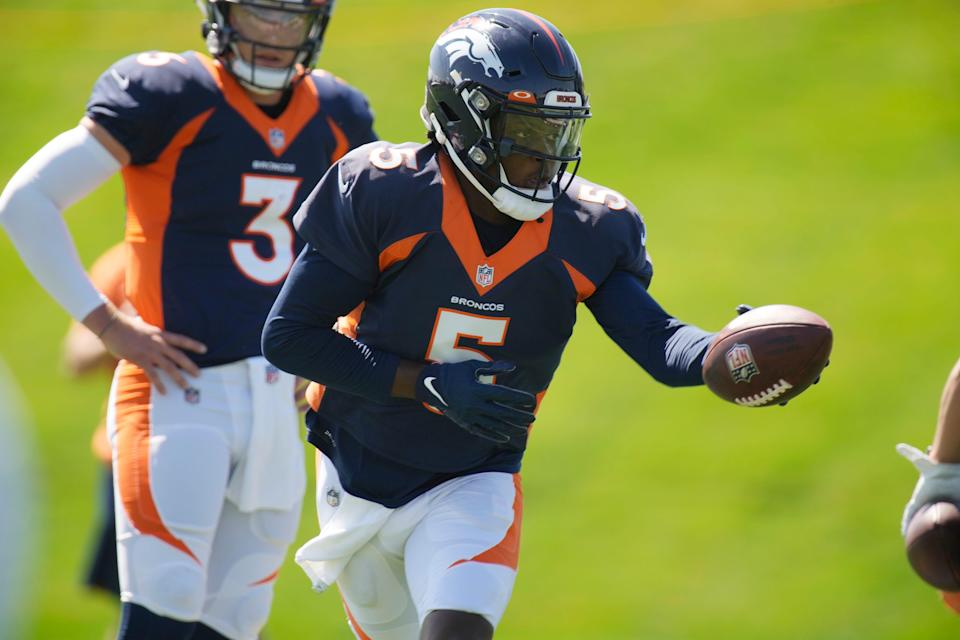 Denver Broncos quarterback Teddy Bridgewater, front, takes part in drills as quarterback Drew Lock looks on during NFL football practice at the team's headquarters Wednesday, Aug. 25, 2021, in Englewood, Colo.