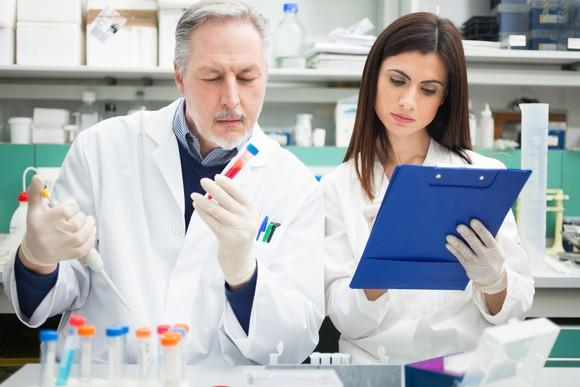 Two biotech lab researchers examining samples and making notes.