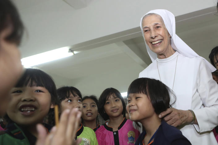 In this Aug. 27, 2019, photo, ST. Mary's School Vice Principal Sister Ana Rosa Sivori, right, talks to students during a lunch break at the girls' school in Udon Thani, about 570 kilometers (355 miles) northeast of Bangkok, Thailand. Sister Ana Rosa Sivori, originally from Buenos Aires in Argentina, shares a great-grandfather with Jorge Mario Bergoglio, who, six years ago, became Pope Francis. So, she and the pontiff are second cousins. (AP Photo/Sakchai Lalit)