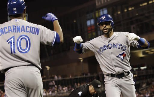 Toronto Blue Jays' Jose Bautista, right, celebrates with teammate Edwin Encarnacion after hitting a solo home run off Minnesota Twins pitcher Nick Blackburn in the first inning of a baseball game on Friday, May 11, 2012, in Minneapolis. (AP Photo/Jim Mone)