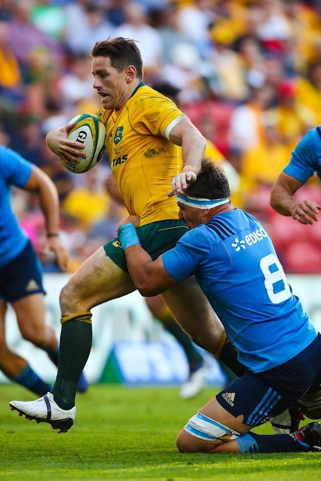 Bernard Foley (L) of Australia is tackled by Andries Van Schalkwyk (R) of Italy during the international rugby match between Australia and Italy at Suncorp Stadium in Brisbane on June 24, 2017. (AFP Photo/Patrick HAMILTON)
