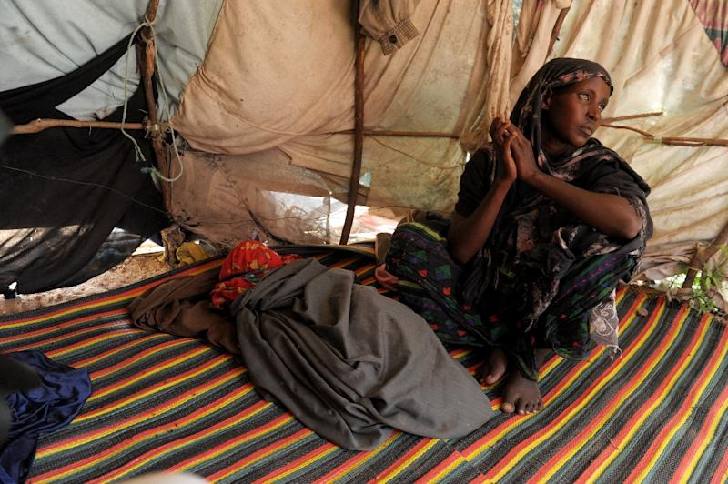 Mulmillo sits inside a makeshift shelter next to the body of her two-year-old son moments after she brought his body back from a Mogadishu hospital, Somalia, 15, 2011 (AFP Photo/Roberto Schmidt)