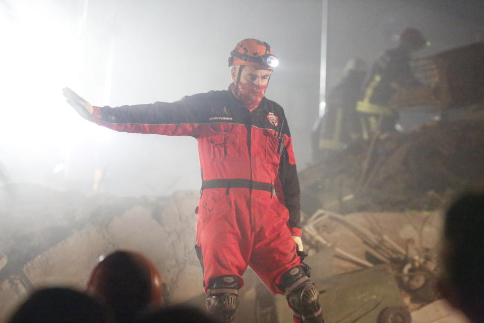 In this photo provided by Turkey's IHH humanitarian aid group, a member of rescue services, guides others during searching for survivors in the debris of a collapsed building in Izmir, Turkey, early Saturday, Oct. 31, 2020. Rescue teams continue ploughing through concrete blocs and debris of collapsed buildings in Turkey's third largest city in search of survivors of a powerful earthquake that struck Turkey's Aegean coast and north of the Greek island of Samos, Friday Oct. 30, killing dozens Hundreds of others were injured. (IHH via AP)