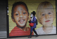 A woman wears protective face coverings as she passes the shutters of a closed shop in West Ealing in London, Thursday, Feb. 25, 2021. It has been announced that further testing of residents in the London Borough of Ealing will be carried out after additional cases of the coronavirus variant first identified in South Africa were detected. (AP Photo/Kirsty Wigglesworth)