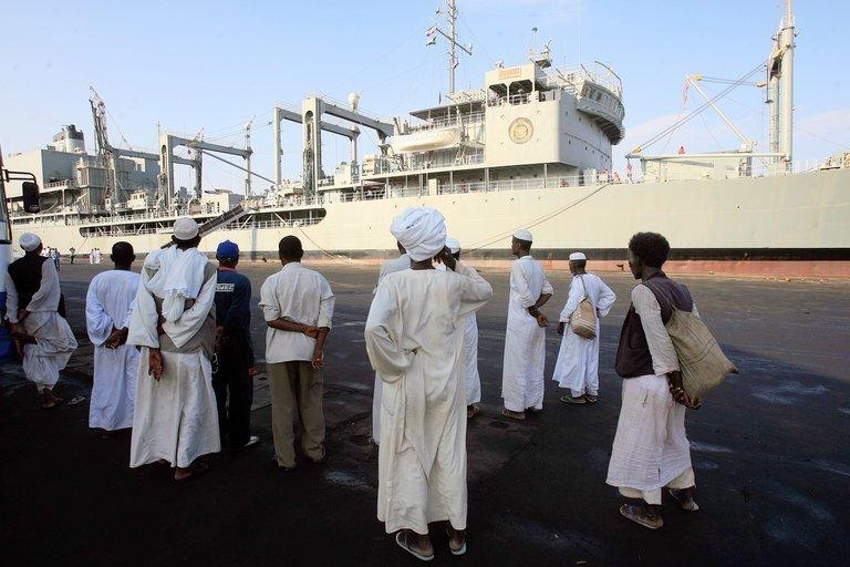 Sudanese stand watching sailors on the Iranian Kharg replenishment ship docked in Port Sudan, in. Two Iranian warships docked in Port Sudan on Saturday, a witness said, marking the second port call by the Iranian navy in Sudan in five weeks
