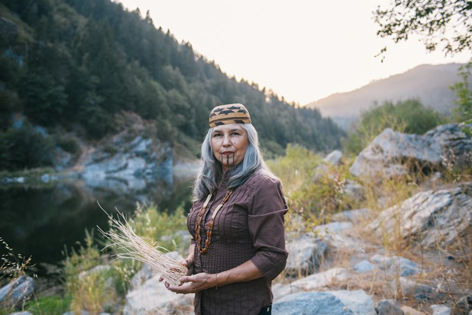 Margo Robbins holds a basket she is in the process of making from fire-dependent resources in Weitchpec, Calif., in front of the Klamath River. (Alexandra Hootnick for Yahoo News)