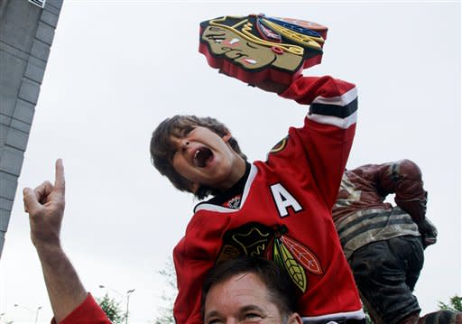 Frank Oberheide rides on the shoulders of his father Jim Oberheide before Game 5 of the NHL hockey Stanley Cup Finals against the Boston Bruins, Saturday, June 22, 2013, in Chicago. (AP Photo/Nam Y. Huh)