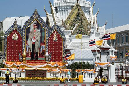 People stand in front of a portrait of Thailand's King Maha Vajiralongkorn during a rehearsal of his coronation procession which will take place next week in Bangkok, Thailand April 28, 2019. REUTERS/Jorge Silva