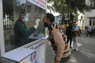 A health worker collects a nasal swab sample to test for COVID-19 at a government hospital in Jammu, India, Thursday, Oct.29, 2020. India's confirmed coronavirus caseload surpassed 8 million on Thursday with daily infections dipping to the lowest level this week, as concerns grew over a major Hindu festival season and winter setting in. (AP Photo/Channi Anand)