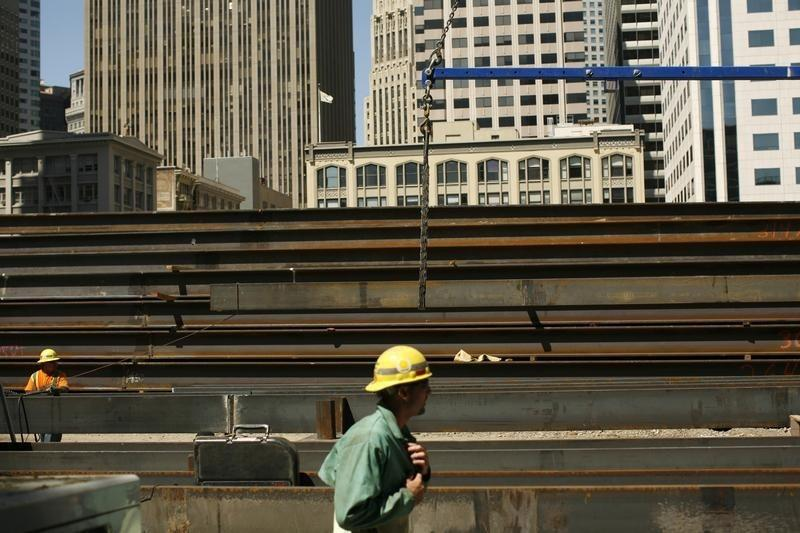 Workers guide steel beams into place at a construction site in San Francisco