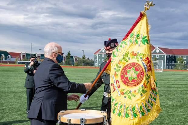 Nova Scotia Lt.-Gov. Arthur LeBlanc, left, presents new colours to the Cape Breton Highlanders Regiment during a change of colours ceremony in Sydney, N.S., on Saturday. (Master Cpl. Trevor Matheson/5th Canadian Division Public Affairs/Department of National Defence - image credit)
