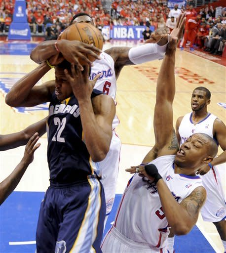 Memphis Grizzlies' Rudy Gay, left, pulls a rebound away from Los Angeles Clippers' DeAndre Jordan, top, and Caron Butler during the first half of a NBA first-round playoff basketball game in Los Angeles, Monday, May 7, 2012. (AP Photo/Chris Carlson)