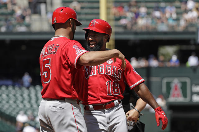 Los Angeles Angels' Albert Pujols, left, greets Brian Goodwin, right, at home on Goodwin's two-run home run against the Seattle Mariners in the fourth inning of a baseball game Sunday, July 21, 2019, in Seattle. (AP Photo/Elaine Thompson)