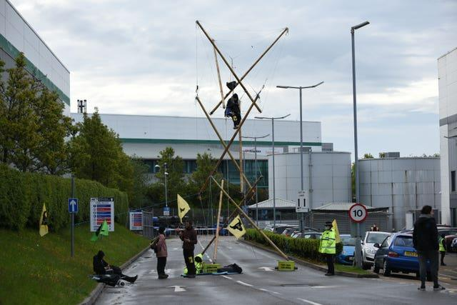 Protesters suspended from a bamboo structure outside a McDonalds distribution site in Basingstoke, Hampshire