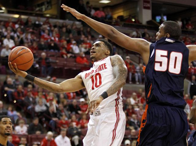 Ohio State's LaQuinton Ross, left, goes up for a shot against Morgan State's Ian Chiles during the first half of an NCAA college basketball game in Columbus, Ohio, Saturday, Nov. 9, 2013. (AP Photo/Paul Vernon)