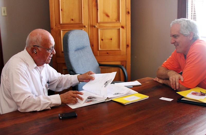 In a Friday, Sept. 7, 2012 photo, activist Javier Diaz, left, 82, shows former Texas state senator Elliot Shapleigh signatures he collected to demand an overhaul of the El Paso Independent School District, in El Paso, Texas. A cheating scandal in which schools would get rid of underperforming students to artificially inflate their high stakes test scores has rocked the El Paso ISD, landed a former superintendent in jail and prompted the Texas Education Agency to put the district on probation.  (AP Photo/Juan Carlos Llorca)