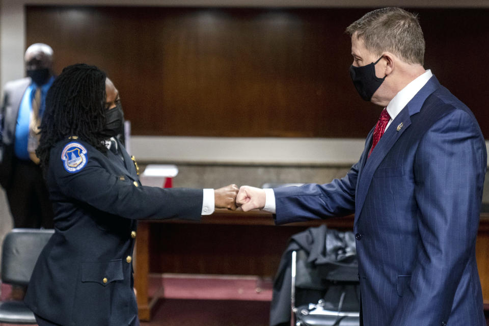 Former U.S. Capitol Police Chief Steven Sund, right, and Capitol Police Captain Carneysha Mendoza, left, greet each other before they testify before a Senate Homeland Security and Governmental Affairs & Senate Rules and Administration joint hearing on Capitol Hill, Washington, Tuesday, Feb. 23, 2021, to examine the January 6th attack on the Capitol. (AP Photo/Andrew Harnik, Pool)