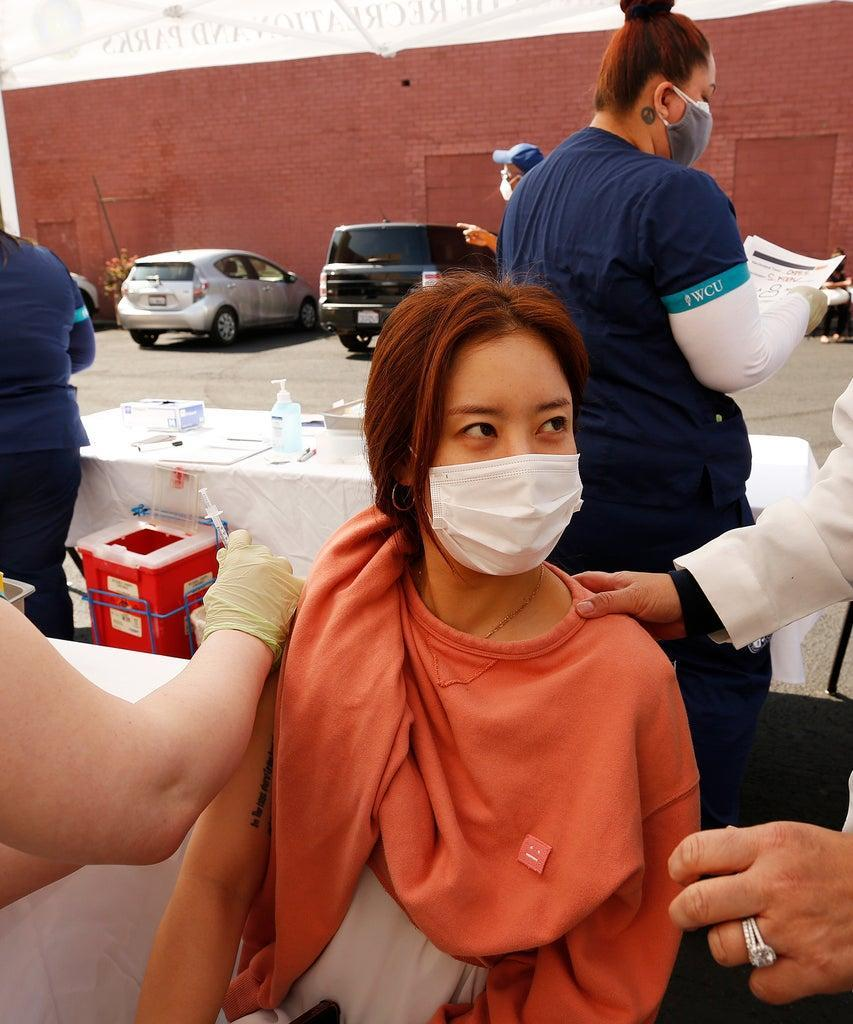 LOS ANGELES, CA – APRIL 20: Luna Paik, 32, is comforted by registered nurse Evangeline Ojales, right, as she receives the Pfizer Covid-19 vaccination from student registered nurse Briana Shaw at a new, walk-up mobile COVID-19 clinic launched today to provide the Pfizer COVID-19 vaccine to underserved communities in Los Angeles. The walk-up clinic was presented by Councilmember Mark Ridley-Thomas in partnership with CHA Hollywood Presbyterian Medical Center (CHA HPMC) and the Southern California Eye Institute (SCEI). The Mobile Vaccine Clinic at 1819 S. Western Avenue will be open every Tuesday starting April 20 through May 25 providing free vaccines to community members who are eligible per LA County Department of Public Health (LAC DPH) vaccine distribution guidelines as they partnered with Charles R. Drew University of Medicine and Science to provide student volunteers for on-site registration allowing for walk-up appointments for community members and further ensuring vaccine access in our hardest-hit communities. Los Angeles on Tuesday, April 20, 2021 in Los Angeles, CA. (Al Seib / Los Angeles Times via Getty Images).