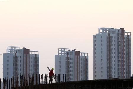 FILE PHOTO: Worker stands on the scaffolding at a construction site against a backdrop of residential buildings in Huaian