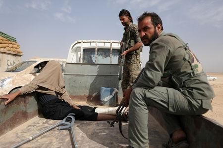 FILE PHOTO: Fighters from Syrian Democratic Forces (SDF) are seen after arresting a wounded man during their fighting with Islamic State in the northern area of Deir al-Zor, Syria