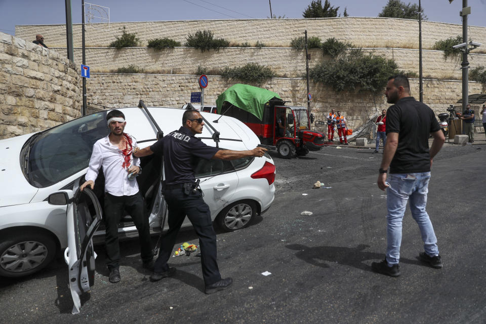 An Israeli police officer protects a Jewish driver who was attacked by Palestinian protesters near Jerusalem's Old City, Monday, May 10, 2021. Israeli police clashed with Palestinian protesters at a flashpoint Jerusalem holy site on Monday. (AP Photo/Ohad Zwigenberg)
