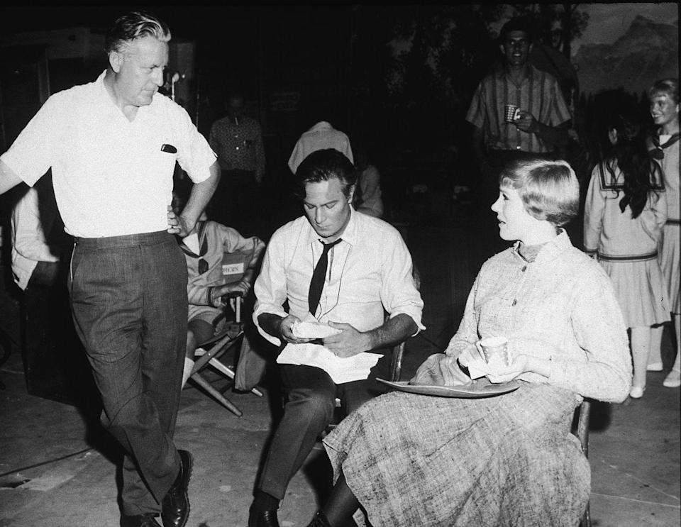 <p>Director Robert Wise chats with actor Christopher Plummer and actress Julie Andrews—who are both in costume—during a lunch break on the set of The Sound of Music.</p>