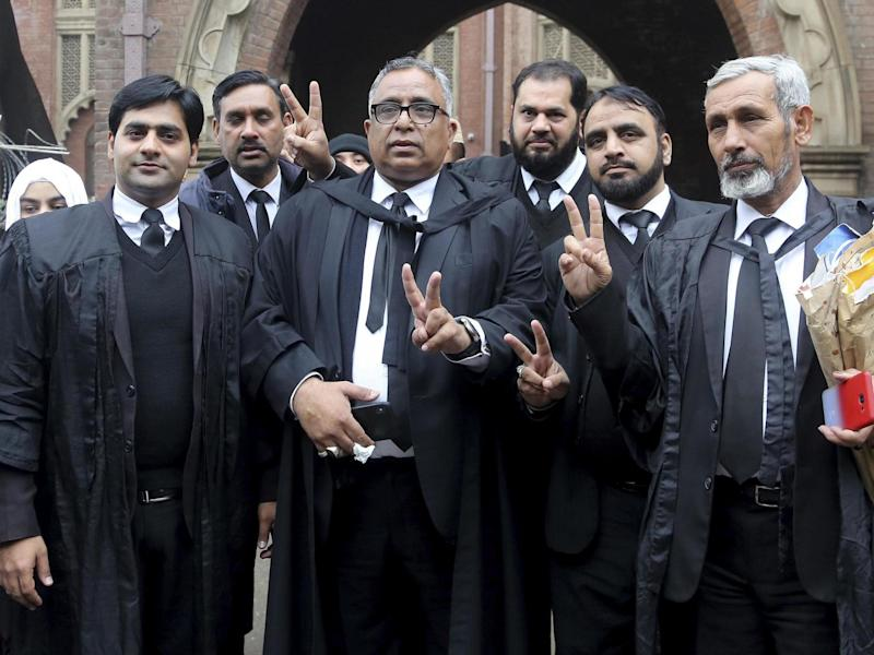 Mohammad Azhar Siddique, center, a lawyer for former Pakistani President and military ruler Pervez Musharraf, and other lawyers make a victory sign after the court decision in Lahore Jan 13 2020: AP