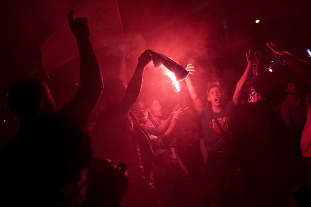 Atletico Madrid supporters light flares as they celebrate their team's Europa League title in Madrid, Wednesday, May 16, 2018. Atletico defeated Marseille 3-0 in the final and clinches its third Europa League title. (AP Photo/Francisco Seco)