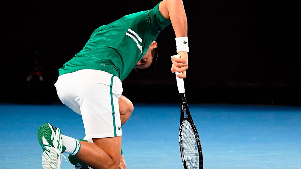 Pictured here, Novak Djokovic goes down on his haunches in agony against Taylor Fritz.