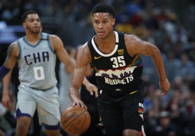 Denver Nuggets guard PJ Dozier, front, brings the ball up as Charlotte Hornets forward Miles Bridges trails during the second half of an NBA basketball game Wednesday, Jan. 15, 2020, in Denver. The Nuggets won 100-86. (AP Photo/David Zalubowski)