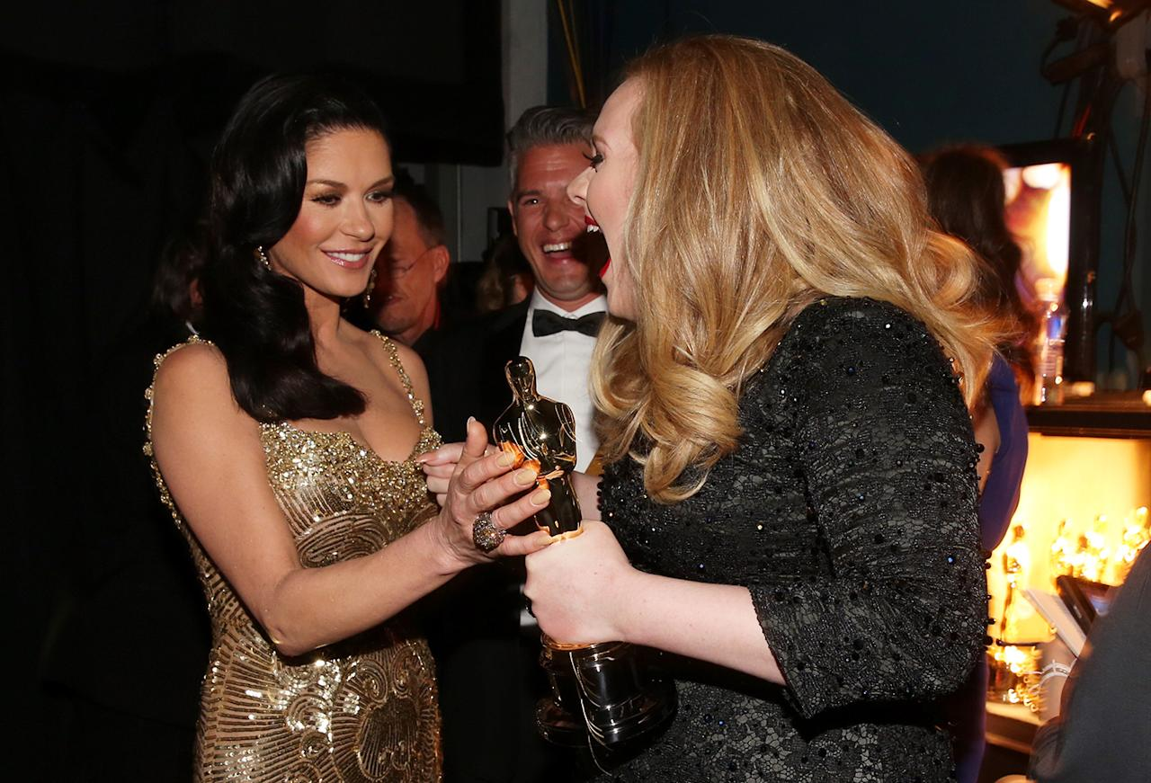 Catherine Zeta-Jones (L) and Adele Adkins, winner of Achievement in Music Written for Motion Pictures- Original Song, backstage during the Oscars held at the Dolby Theatre on February 24, 2013 in Hollywood, California.