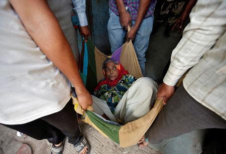 An elderly woman is carried in a blanket after casting her vote at a polling station during the last phase of Gujarat state assembly election in Ahmedabad, India, December 14, 2017. REUTERS/Amit Dave