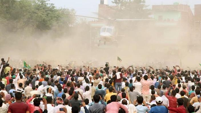 People look on as RJD leader Tejashwi Yadav leaves in a helicopter during an election campaign rally at Masaurhi on October 21, 2020 in Patna