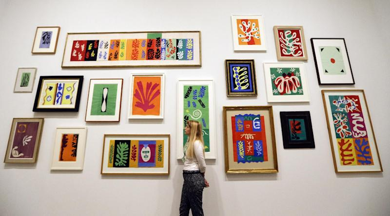 A woman looks at a wall of artworks by Henri Matisse, on display during a media opportunity at The Tate Modern in London, Monday, April 14, 2014. The artworks are part of the 'Henri Matisse: The Cut-Outs' exhibition that runs at the gallery from April 17 until Sept. 7, 2014.(AP Photo/Kirsty Wigglesworth)
