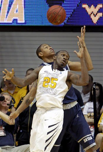 Georgetown's Greg Whittington, rear, and West Virginia's Darryl Bryant (25) fight for a rebound during the first half of an NCAA college basketball game at WVU Coliseum in Morgantown, W.Va., on Saturday, Jan, 7, 2012. (AP Photo/David Smith)