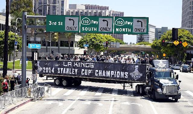 Members of the Los Angeles Kings NHL hockey team ride on the back on a semi truck in a parade through downtown Los Angeles, Monday, June 16, 2014. The parade and rally were held to celebrate the Kings' second Stanley Cup championship in three seasons. The Kings defeated the New York Rangers for the title. (AP Photo/Mark J. Terrill)